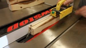 cutting a log into lumber on a table saw
